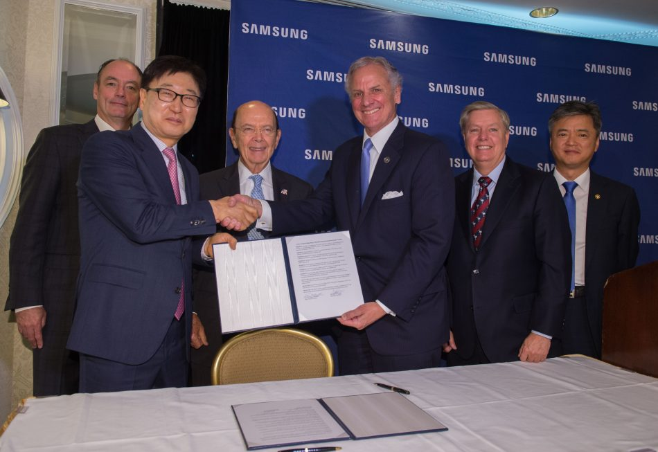 In this photograph provided by Samsung Electronics America, Samsung Electronics America President & CEO Tim Baxter (standing left), Samsung Electronics President & CEO of Consumer Electronics Boo-Keun Yoon (standing second from left), U.S. Secretary of Commerce Wilbur Ross (standing third from left), South Carolina Governor Henry McMaster (standing third from right), Senator Lindsey Graham (standing second from right) and Korean Vice Minister of Trade, Industry & Energy Inho Lee (standing right), announce plans to open a Samsung manufacturing facility in Newberry, S.C., Wednesday June 28th, 2017 in Washington, D.C. The plant is slated to bring 954 jobs to the region by 2020.