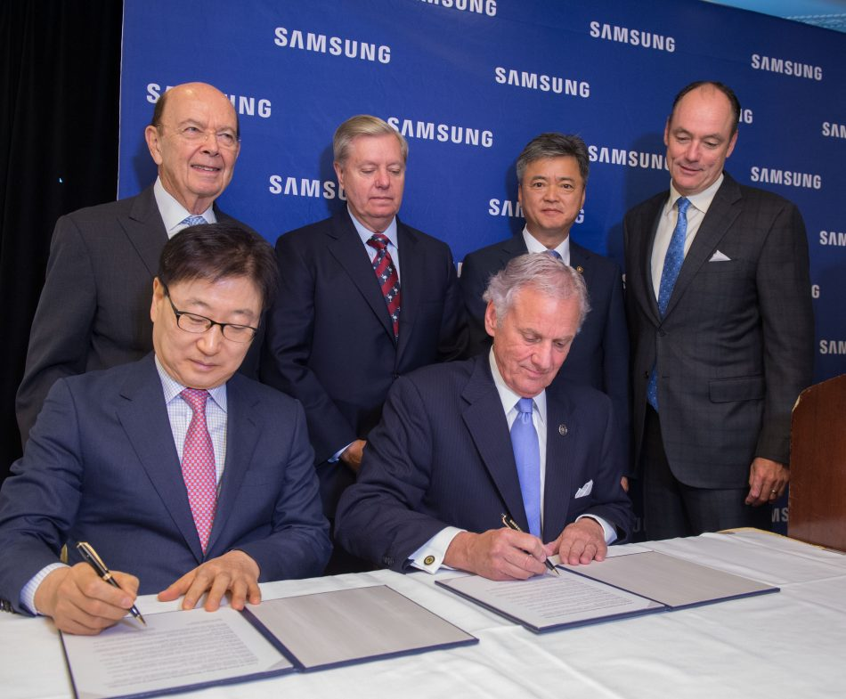 In this photograph provided by Samsung Electronics America, U.S. Secretary of Commerce Wilbur Ross (standing left), Senator Lindsey Graham (standing left center), Korean Vice Minister of Trade, Industry & Energy Inho Lee (standing right center), Samsung Electronics America President & CEO Tim Baxter (standing right), Samsung Electronics President & CEO of Consumer Electronics Boo-Keun Yoon (seated left) and South Carolina Governor Henry McMaster (seated right) announce plans to open a Samsung manufacturing facility in Newberry, S.C., Wednesday June 28th, 2017 in Washington, D.C. The plant is slated to bring 954 jobs to the region by 2020.