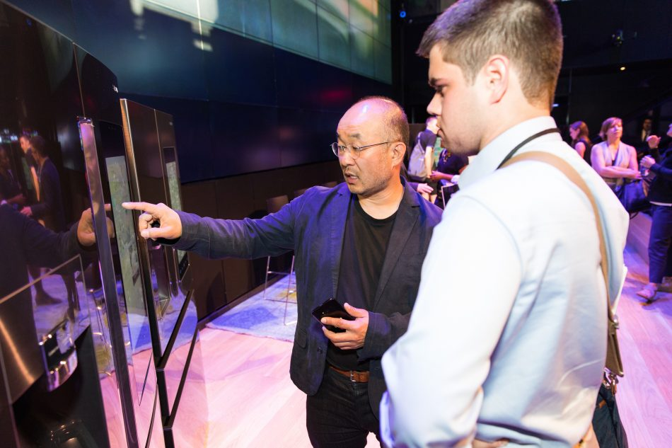 Yoon Lee, Senior Vice President and Head of Product Innovation Team and Content and Services at Samsung Electronics America, showcases new Samsung Family Hub refrigerator to an attendee during Samsung Family Hub 2017 Event and Smart Kitchen Summit.