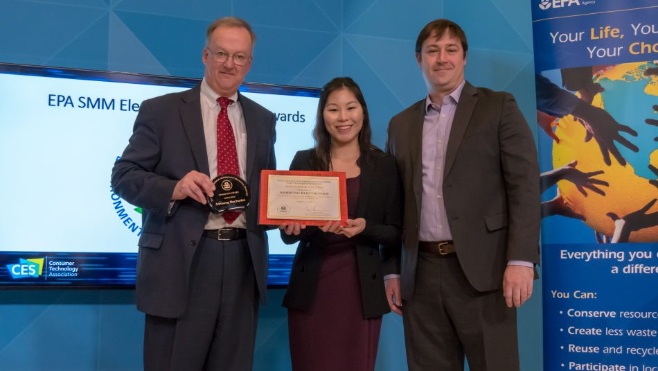 Josh Ives, VP of Customer Experience, and Jenni Chun, Manager of Corporate Regulatory & Environmental Affairs, both of Samsung Electronics America, accept the 2017 Cutting Edge Champion Award and Gold Tier Award for the company's continued sustainability efforts. Presenting the awards was Barnes Johnson, Director of the EPA Office of Resource Conservation and Recovery.