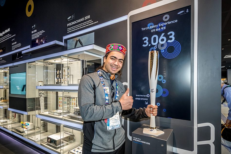 """A true example of """"Do What You Can't,"""" six-time Olympian from India, Shiva Keshavan stops to hold the Olympic torch as he learns about Samsung's 20-year heritage as a Worldwide Partner in the Wireless Communications Equipment category while visiting the Samsung Olympic Showcase in Gangneung Olympic Park in South Korea during the Olympic Winter Games PyeongChang 2018."""