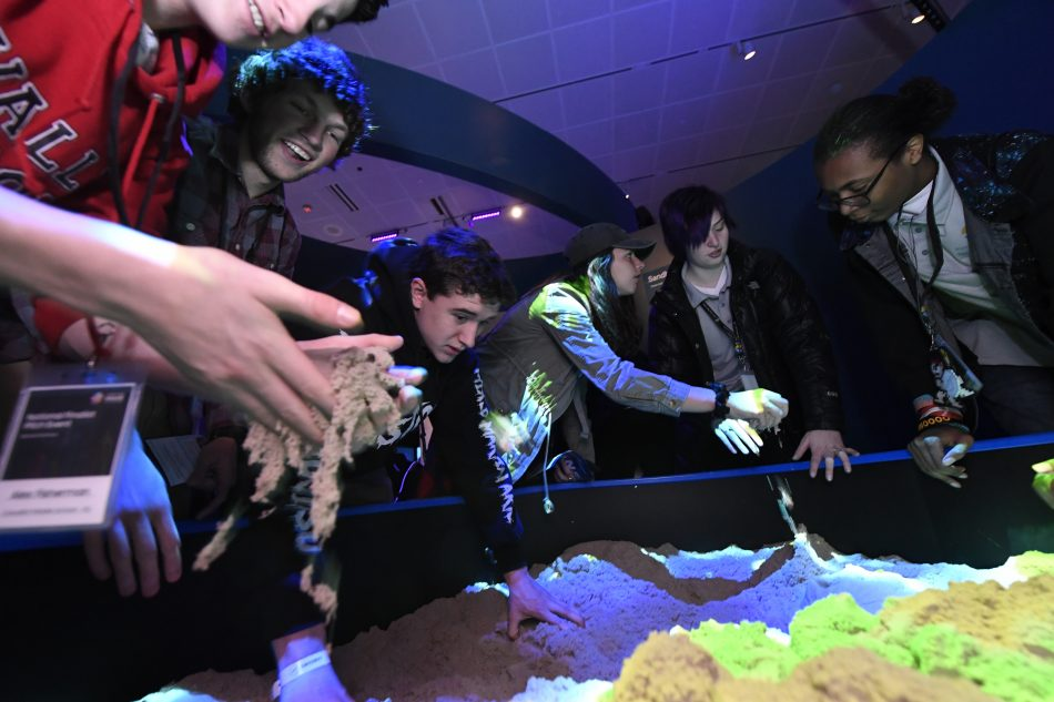 Students from the ten National Finalist schools play with sand at the Unseen Oceans exhibit at the American Museum of Natural History in New York City on Tuesday, April 10, 2018.