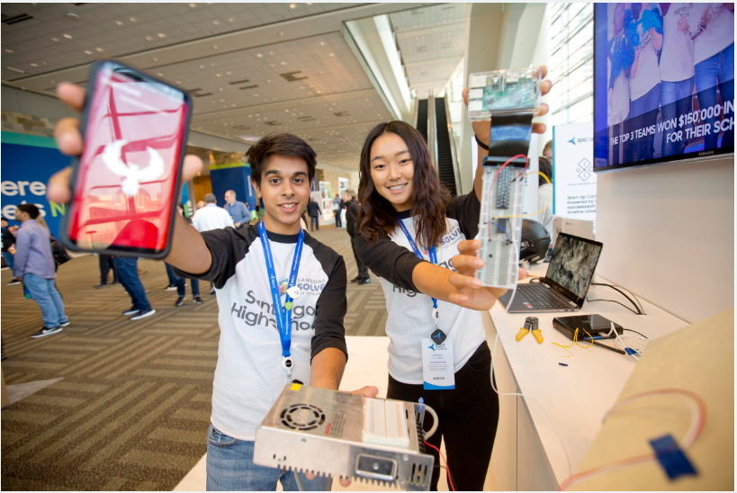 "From L to R: Harshil P. and Lauren S., former students at Santiago High School in California, show off their ""Project Phoenix"" app and prototype for protecting structures from wildfires, which was developed with guidance from their teacher, Doloumar Bergen, during the Samsung Solve for Tomorrow 2017-18 contest year. SDC 2018"