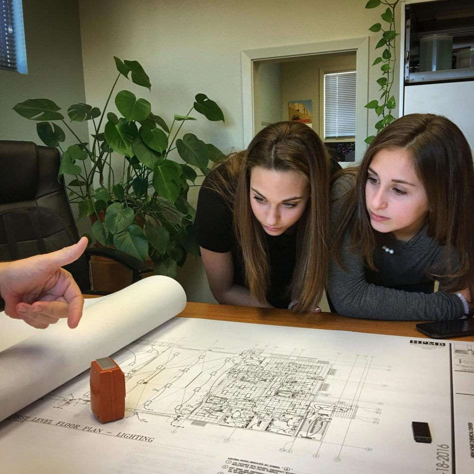 Architect Plans.jpg Caption: Garcia's students Brianna R. (left) and Arianna B. (right) learn about lighting plans from an architect during the ideation phase of their Solve for Tomorrow project for a natural-disaster housing concept.