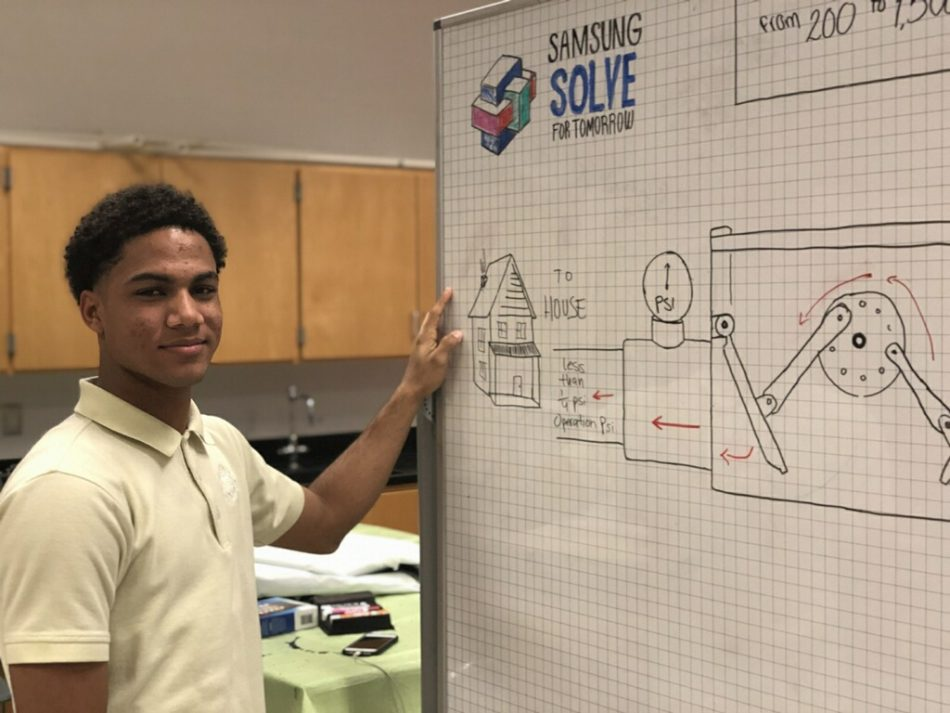 Jhovany M., a student from ENLACE at Lawrence High School in Lawrence, MA, with a whiteboard diagram of the team's gas safety valve project idea.