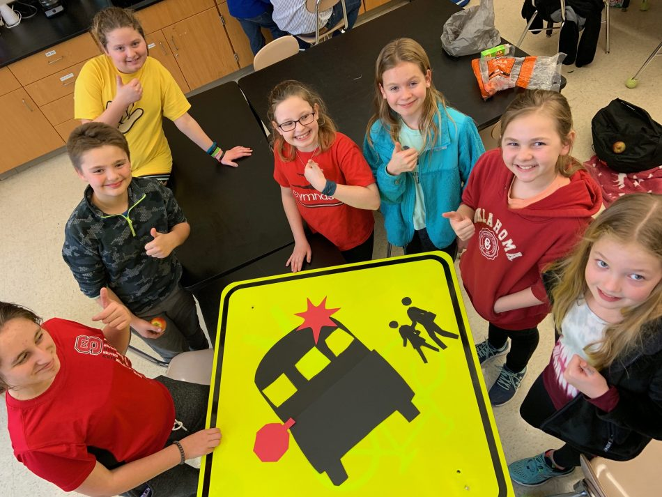 The team from Holly Grove Middle School in Holly Springs, NC, with their smart school bus sign, designed to prevent pedestrian accidents by alerting drivers even before the bus arrives.