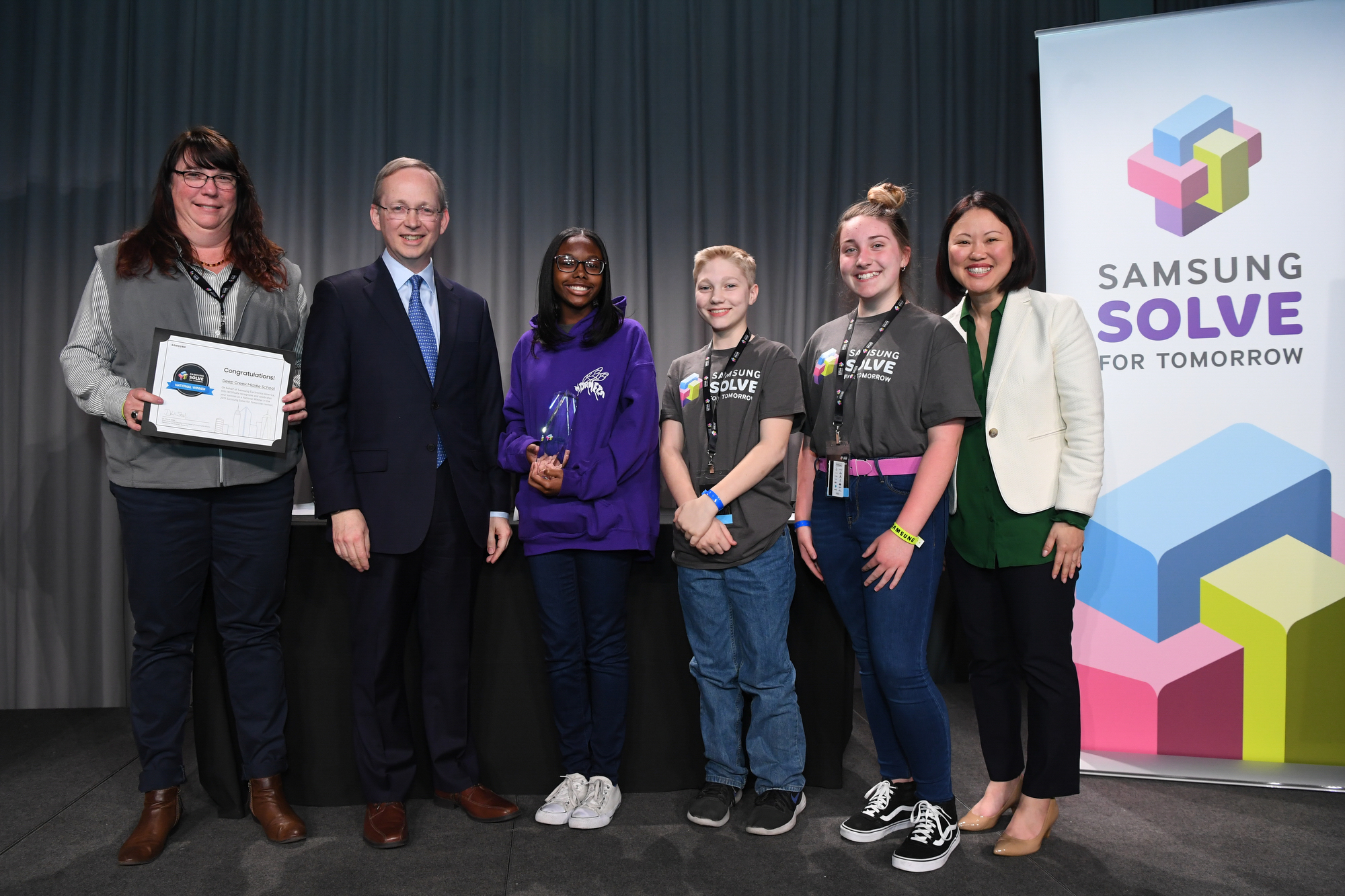 Deep Creek Middle School in Chesapeake, Virginia was named a 2019 national winner in the Samsung Solve for Tomorrow Contest at a ceremony on Tuesday, April 2, 2019 at the Intrepid Sea, Air & Space Museum in New York City. Teacher Paula Labbe and students Olivia Lyons, Hunter Johnston and Tia Davis received the award from Samsung's Dr. David Steel, EVP and Head of Corporate Affairs and Ann Woo, Senior Director of Corporate Citizenship. The students won for creating a website and app for high-need students with poor vision to access free prescription glasses.