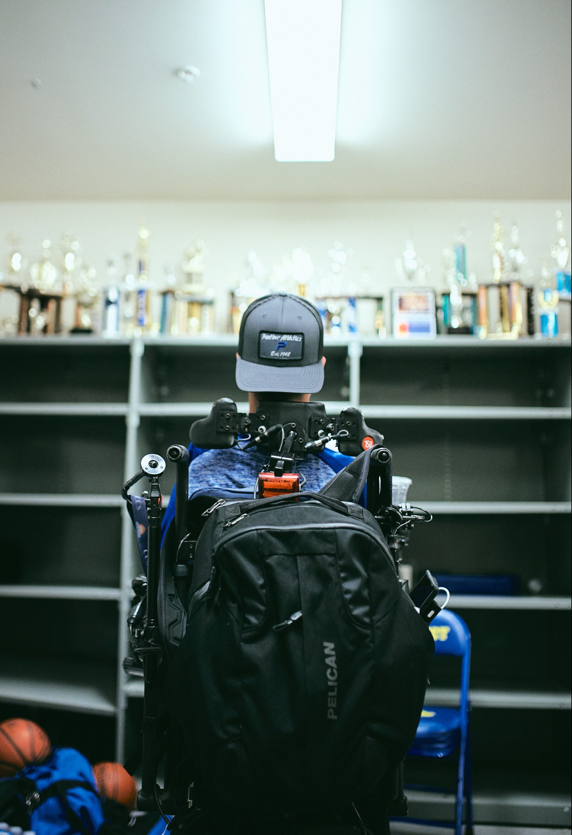 Caption: Coach Rob Mendez stares at the wall of trophies at Prospect High School in Saragota, California.