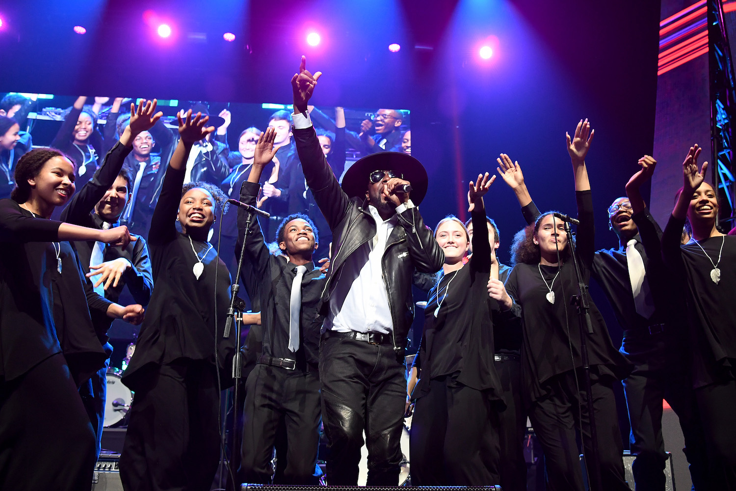 Philanthropic musician DJ Irie, representing the Irie Foundation, and Grammy Award-winning hip hop star Wyclef Jean get the audience dancing to kick off the evening, accompanied by the Young People's Chorus of New York.