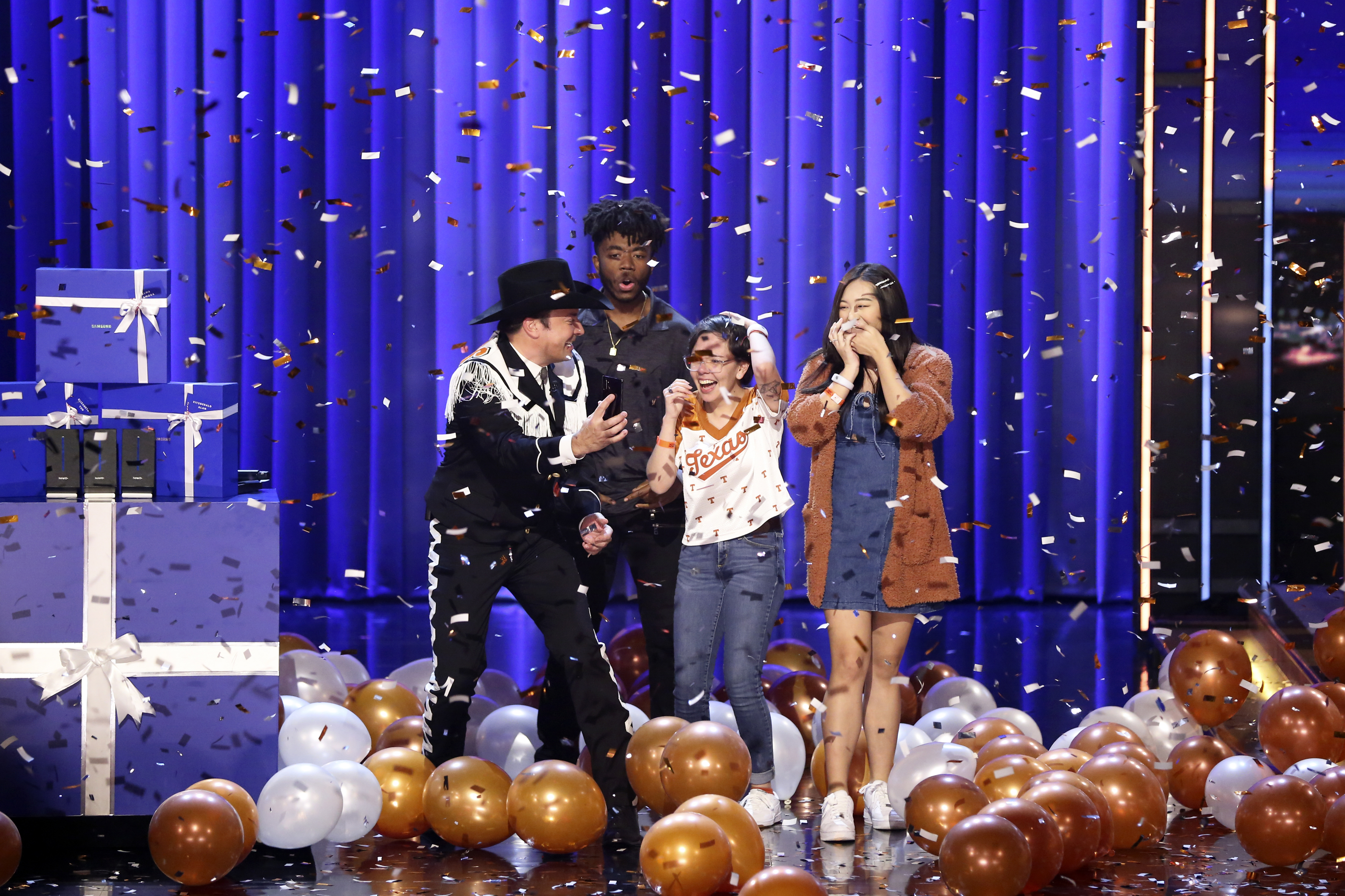"(L-R) Host Jimmy Fallon with UT Austin Students Fitzgerald Alan, Alma Zamora, and Elizabeth Yoon during the ""Samsung Phone Giveaway"" on November 7, 2019 -- (Photo by: Andrew Lipovsky/NBC)"