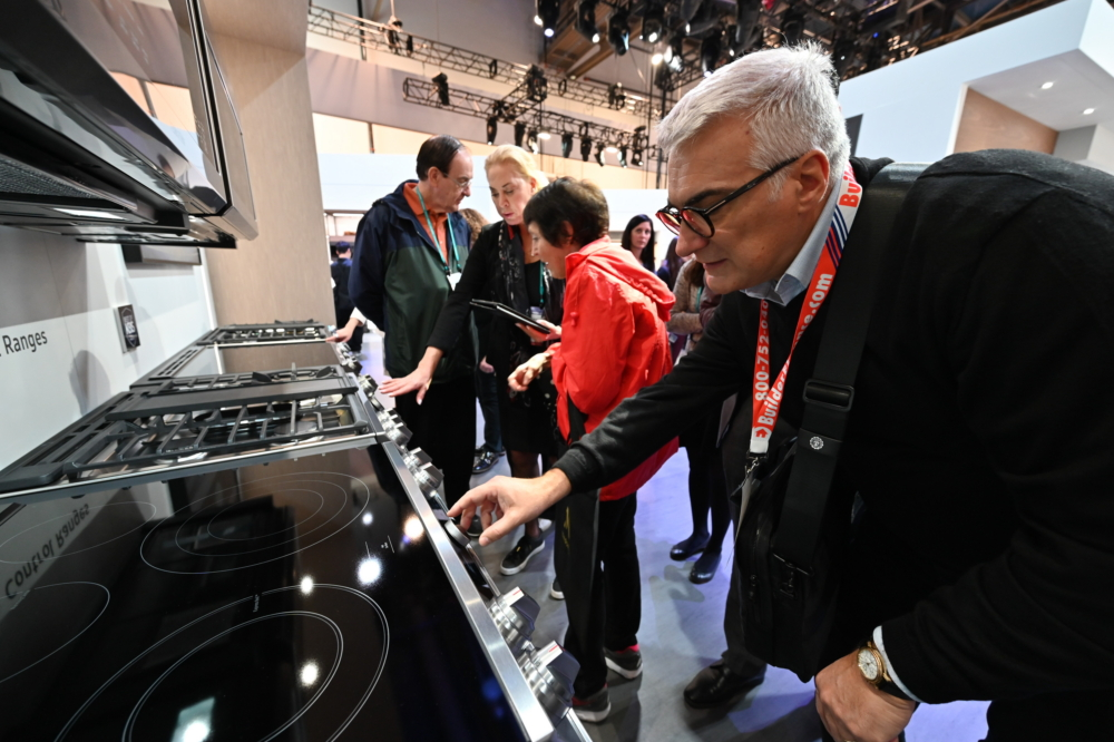 "A KBIS visitor explores the different capabilities and smart features of the Samsung 30"" Slide-in Range"