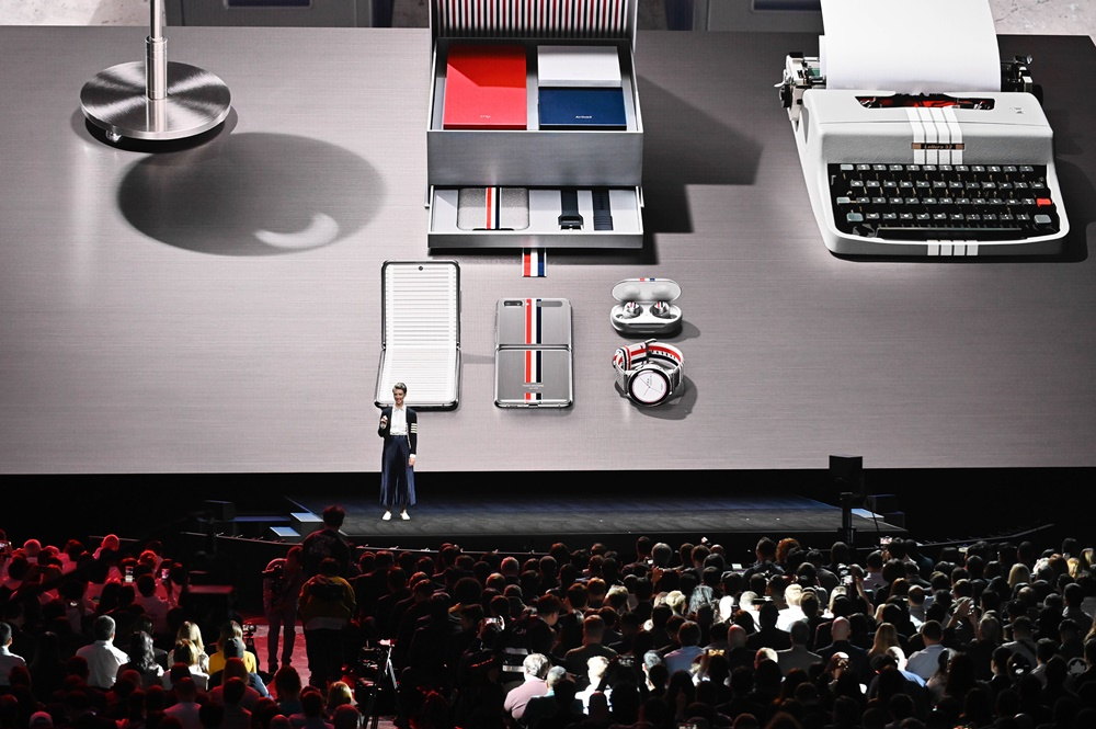 """Hirst introduces the crowd to the Galaxy Z Flip Thom Browne Edition. Created in partnership with the renowned fashion designer, the device proves once and for all that """"high fashion and high-tech go hand in hand."""""""