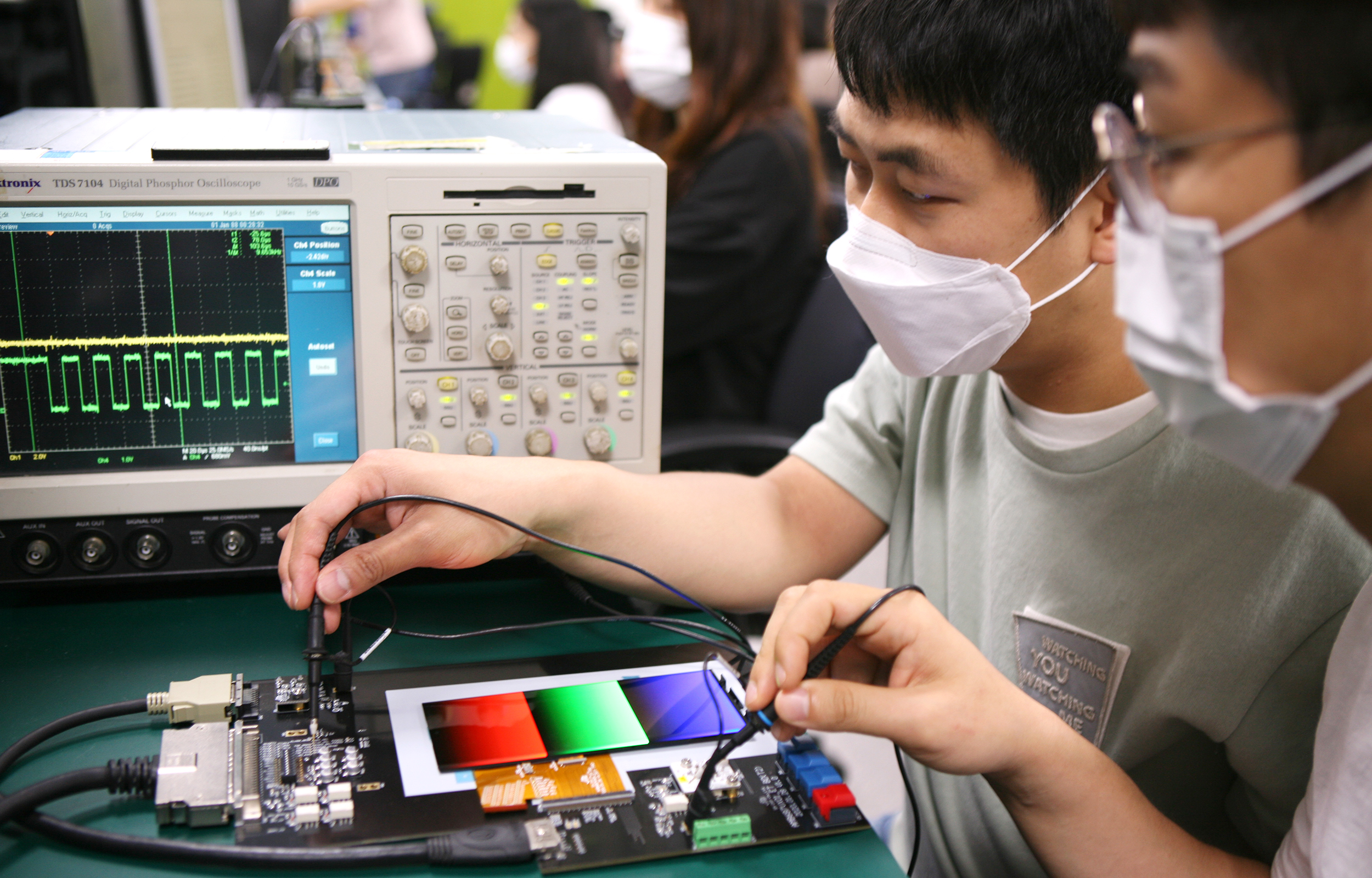 Engineers from Samsung Display are using testing devices to inspect frequency changes in display panels that feature adaptive frequency technology.